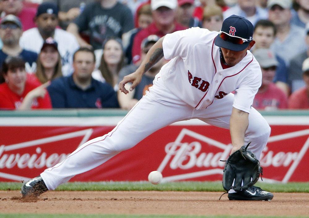 Boston Red Sox's Tzu-Wei Lin fields a ground ball by Chase Headley of the Yankees during the fourth inning of Saturday's game in Boston. But it was a long way from over in the fourth inning. The Yankees scored three runs in the 16th inning and went to beat the Red Sox 4-1. (Associated Press/Michael Dwyer)