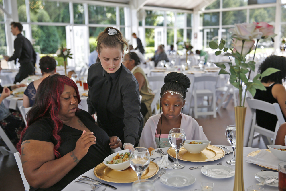 Katelin Decraene, center, serves Trishell Crawford and her daughter Jacqueline Crawford at the reception.