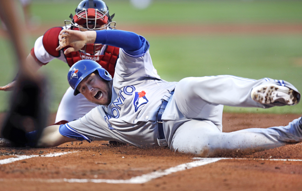 The Blue Jays' Justin Smoak beats the tag by Red Sox catcher Christian Vazquez to score on a two-run double by Kendrys Morales in the first inning.