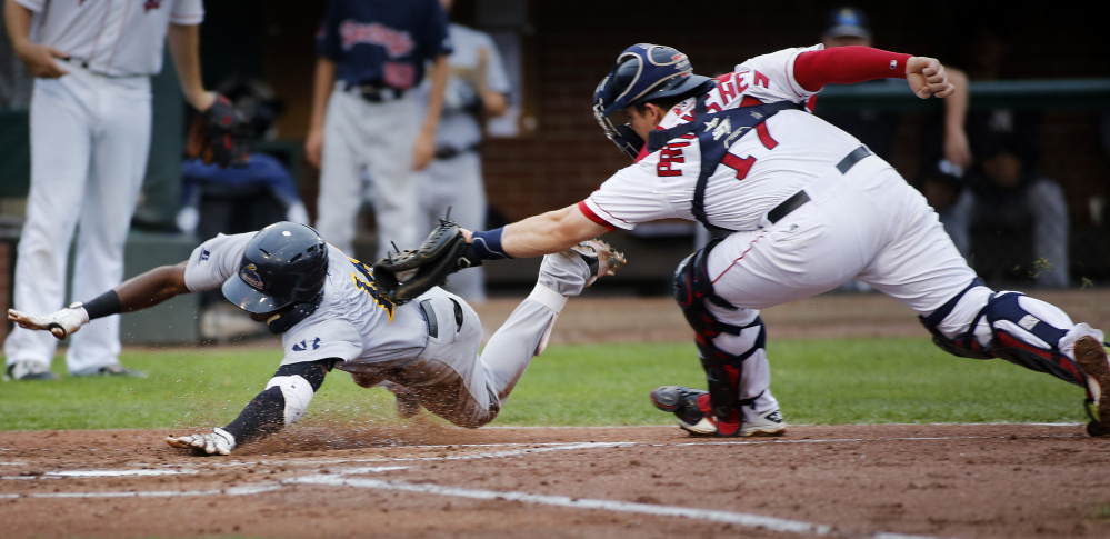 Jorge Mateo of the Trenton Thunder is tagged out by Sea Dogs catcher Jordan Procyshen as he tries to score in the third inning Monday night at Hadlock Field. Trenton scored four runs in the sixth to rally for a 4-3 win.