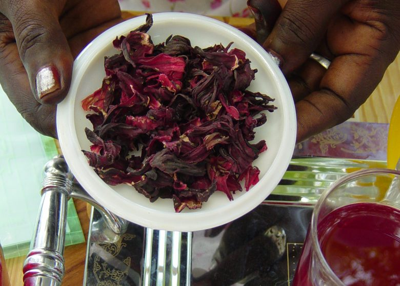 A woman holds karkaday, hibiscus petal tea, next to a glass of it prepared and presented on a silver tray. In Sudan the tea is often cold-brewed, then strained, and served as a cool drink to counter the heat.