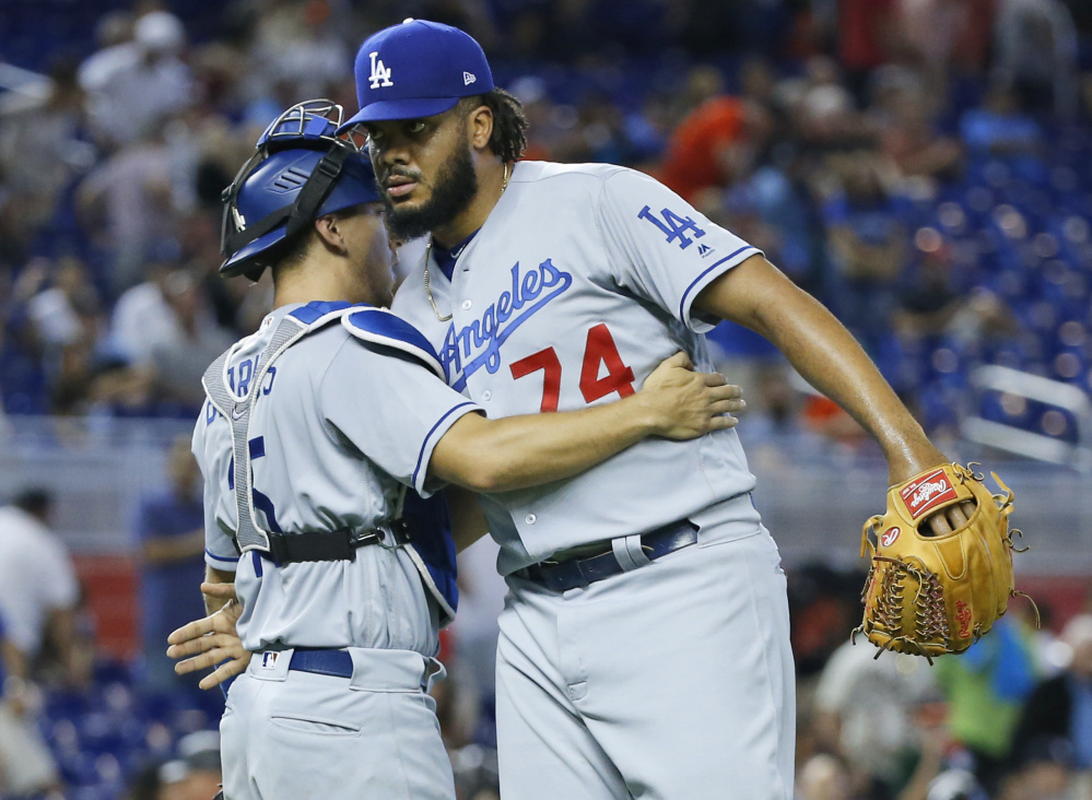 Closer Kenley Jansen gets congratulated by catcher Austin Barnes on Sunday in Miami after the Los Angeles Dodgers won their ninth straight game.