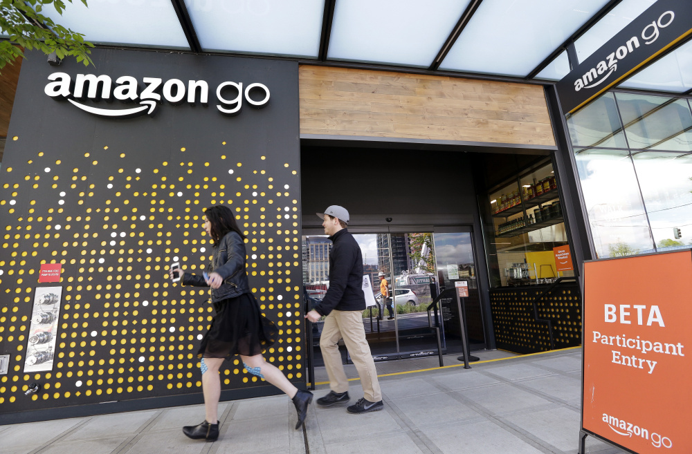 People walk past an Amazon Go store in Seattle last April, where the company is experimenting with new offerings, including Amazon-branded meal kits. The development comes as Amazon is also buying Whole Foods for $13.7 bilion.