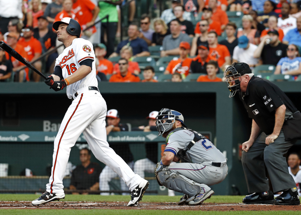Trey Mancini of the Baltimore Orioles watches his two-run homer head to the stands in front of Texas catcher Jonathan Lucroy and umpire Brian Gorman during the Orioles' 12-1 victory Tuesday.