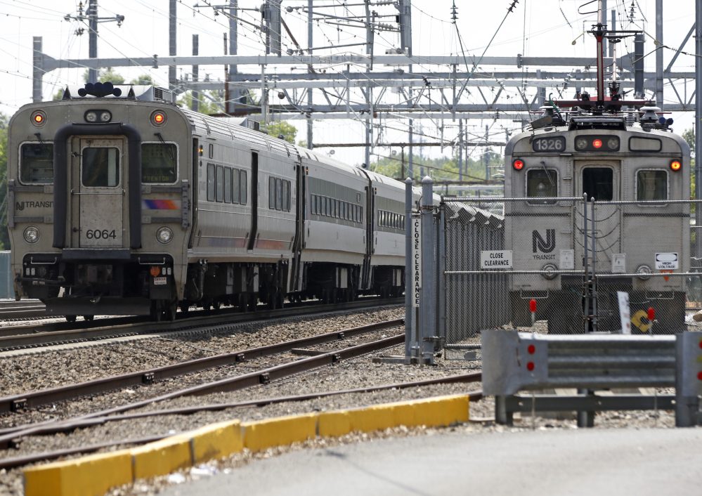 A New Jersey Transit train, left, passes by the sidelined Princeton Dinky train, right, Tuesday, in West Windsor, N.J. Some trains, including the Dinky, were canceled this week during summerlong repair work at New York's Penn Station, the nation's busiest train station.