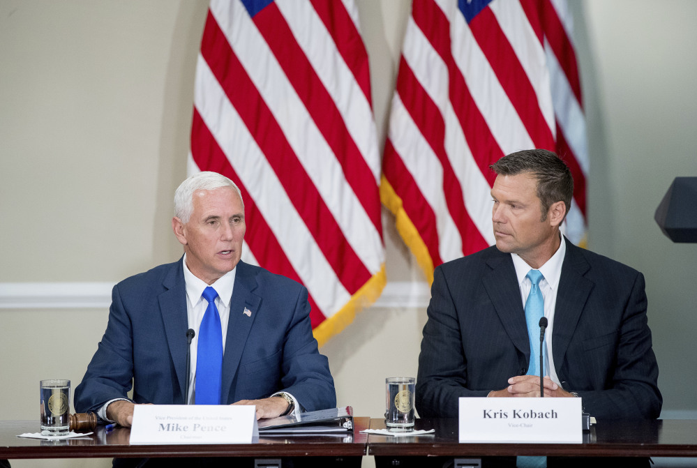 Vice President Mike Pence, left, with Kansas Secretary of State Kris Kobach, speaks during the meeting of the president's voter fraud panel in July.