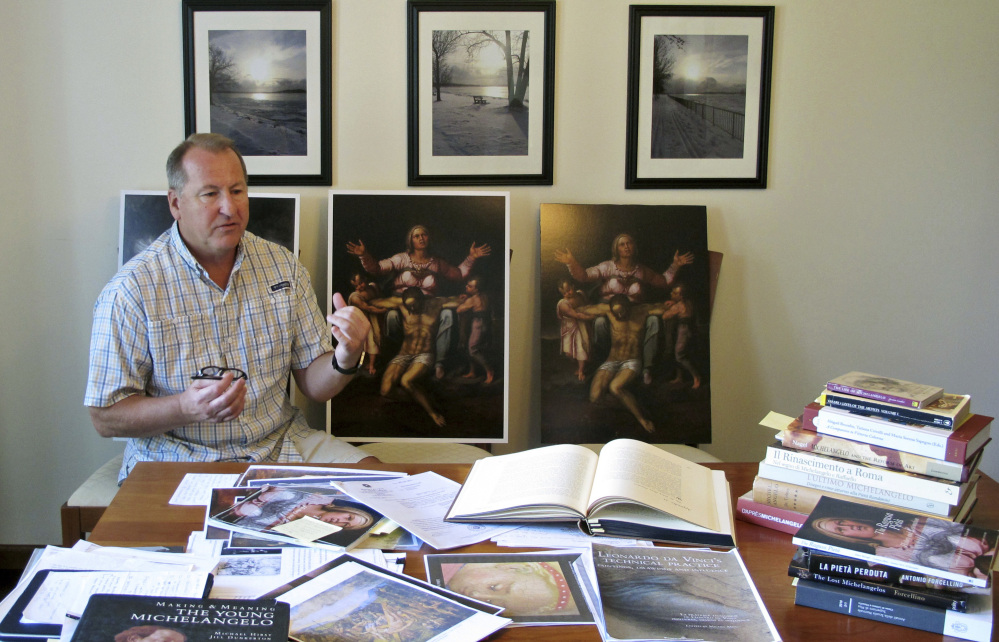 Martin Kober displays literature and copies of a family heirloom that he believes was painted by Renaissance master Michelangelo.