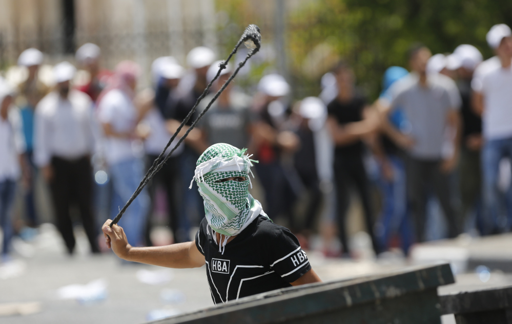 A Palestinian uses a slingshot against Israeli soldiers during clashes Bethlehem on Friday. At issue are metal detectors Israel installed at a Jerusalem shrine earlier this week.