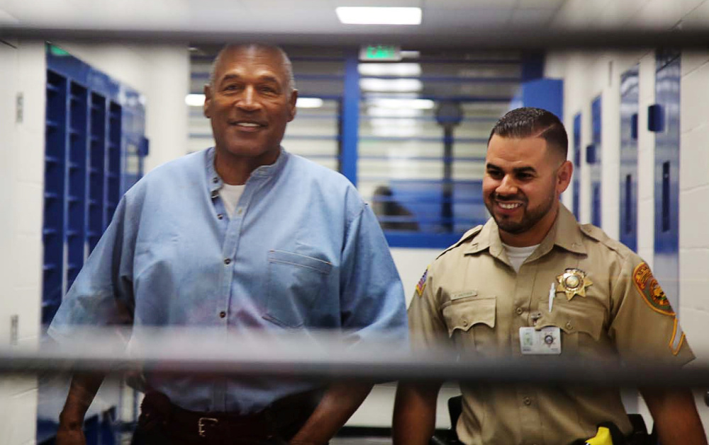 Above, O.J. Simpson is all smiles as he's escorted by a correctional officer for his parole hearing Thursday in Lovlock, Nev., just as he was all smiles when acquitted of a double-murder charge in 1995 with the help of a top-notch defense team that included attorneys F. Lee Bailey, left, and the late Johnnie Cochran Jr.