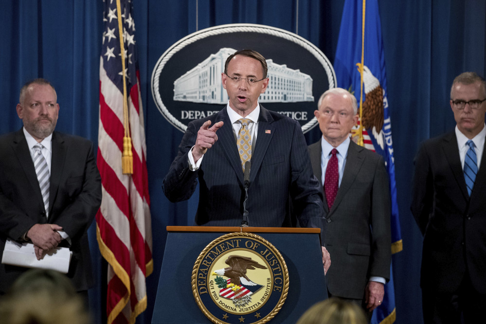 Deputy Attorney General Rod Rosenstein, center, accompanied by DEA Deputy Administrator Robert Patterson, left, Attorney General Jeff Sessions, second from right, and FBI Acting Director Andrew McCabe announce an international cybercrime enforcement action Thursday at the Department of Justice in Washington, D.C.