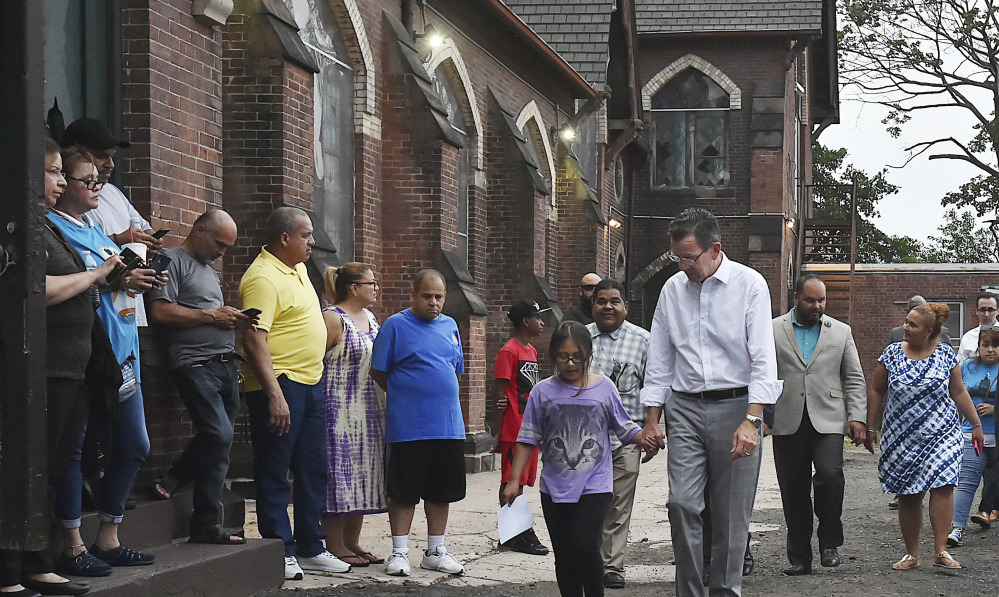 Connecticut Gov. Dannel P. Malloy walks with 9-year-old Hayley Chavarria before speaking at a Thursday news conference at Iglesia de Dios Pentecostal Church in New Haven, where her mother has taken sanctuary to avoid deportation.