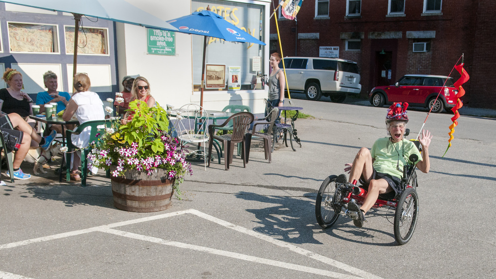 Maggie Warren, 71, of Hallowell, pedals her recumbent bicycle Friday at Slate's Bakery in downtown Hallowell. The outdoor tables are an early morning gathering place.