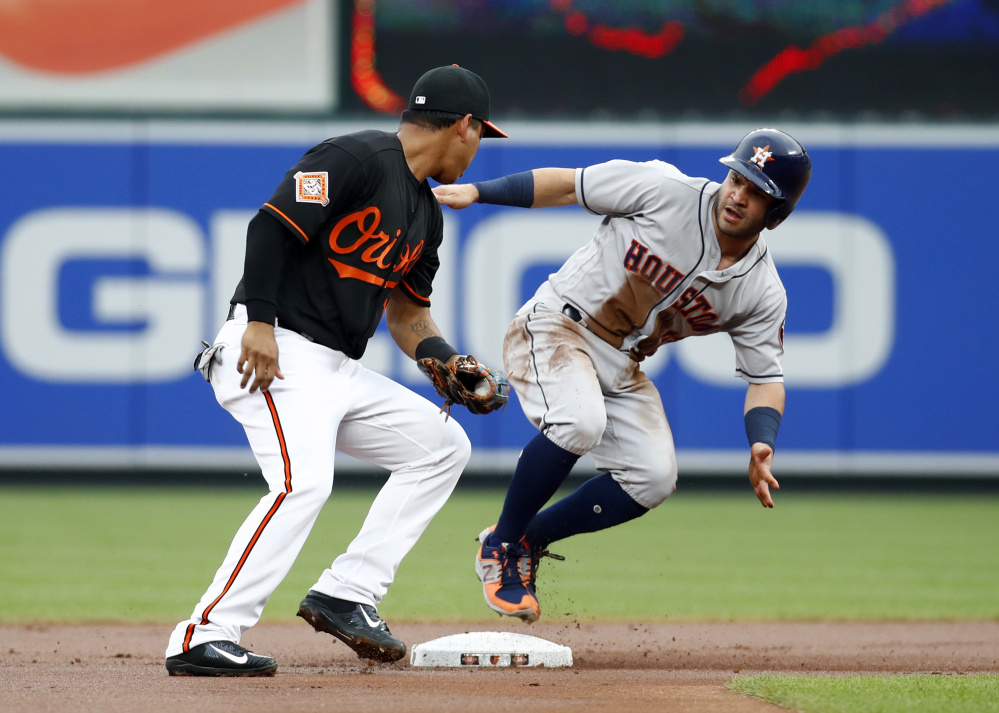 Jose Altuve of the Houston Astros, right, steals second base as Ruben Tejada of the Baltimore Orioles takes the throw Friday night in the first inning of Houston's 8-7 victory.
