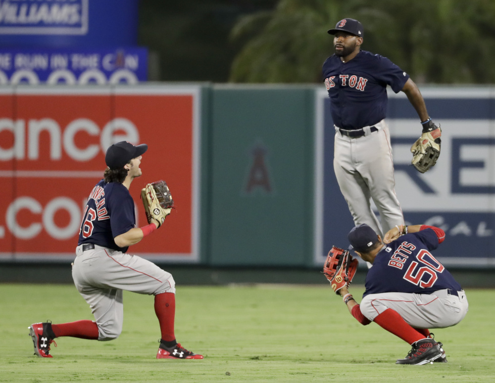 Red Sox left fielder Andrew Benintendi (left) center fielder Jackie Bradley Jr. and right fielder Mookie Betts celebrate the team's 6-2 win over the Angels.