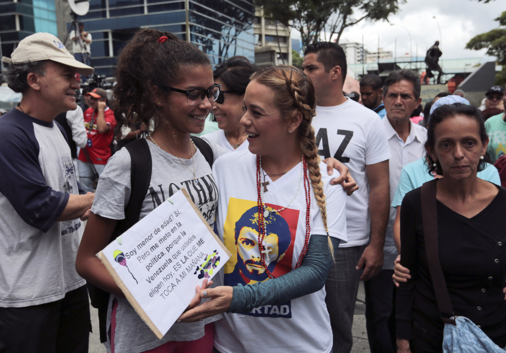 Lilian Tintori, right center, wife of opposition leader Leopoldo Lopez, greets an anti-government protester at a march to the Supreme Court in Caracas on Saturday.