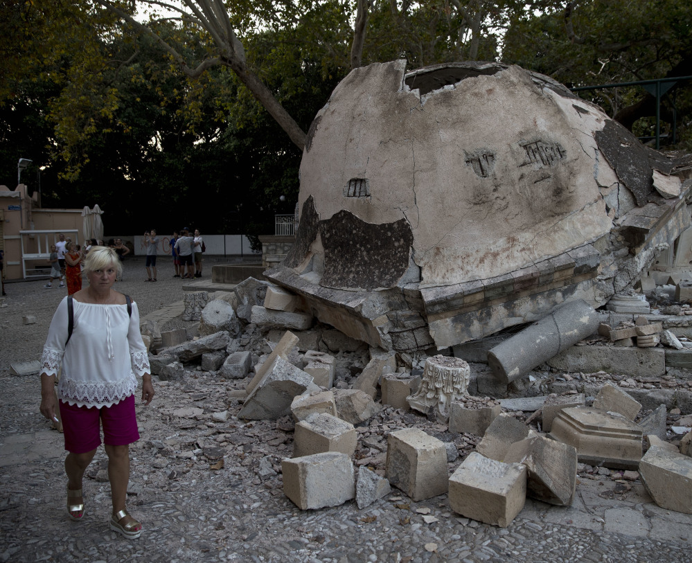 A tourist walks past a damaged structure outside a mosque after an earthquake on the Greek island of Kos. Hundreds of people on Kos spent the night sleeping outdoors.
