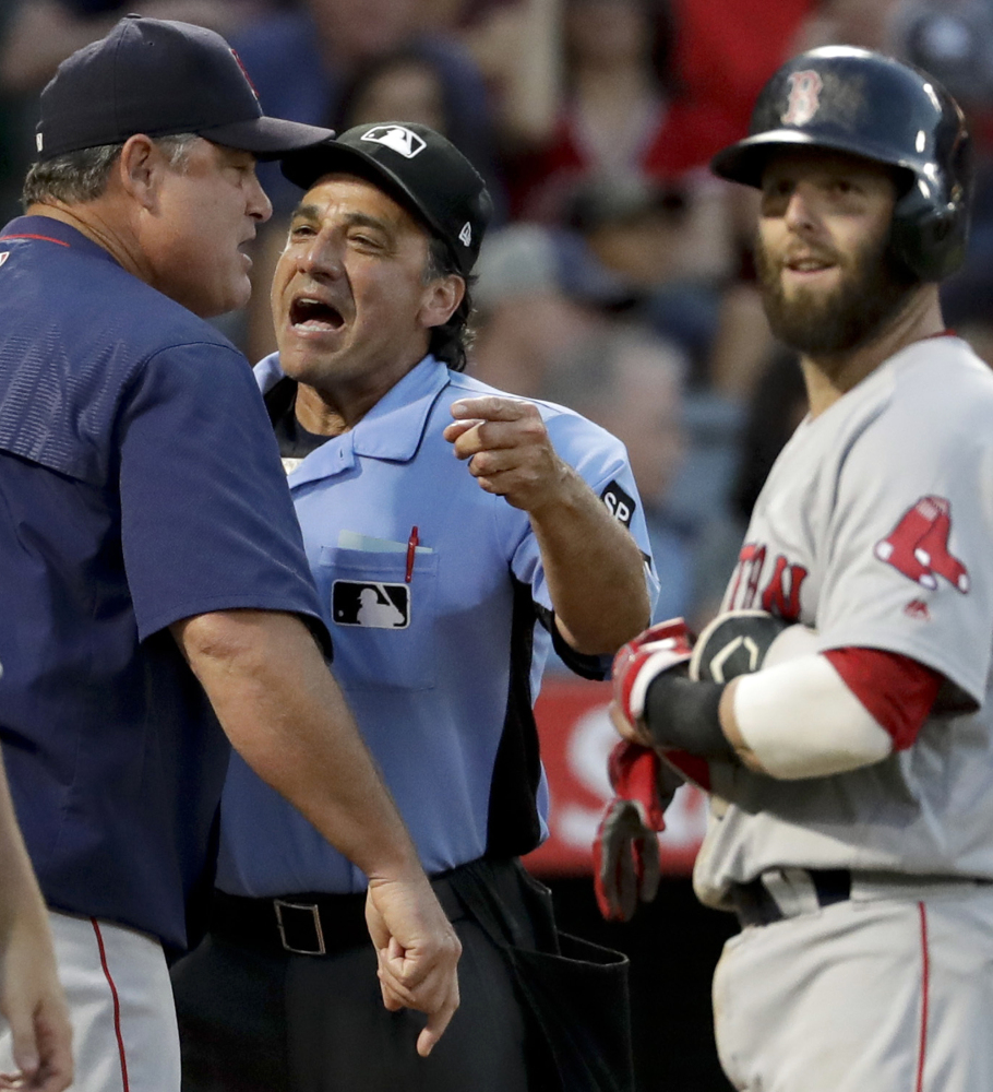 Boston manager John Farrell argues a call with home plate umpire Phil Cuzzi as Dustin Pedroia looks on during the fifth inning Saturday night in Anaheim. The Red Sox lost 7-3.