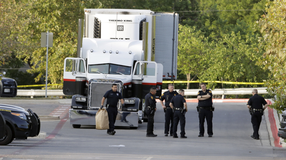 San Antonio police officers investigate the scene after eight people were found dead in a tractor-trailer.