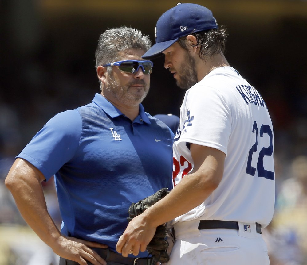 Dodgers starting pitcher Clayton Kershaw, right, talks with trainer Nathan Lucero in the second inning Sunday. Kershaw left with a back injury.