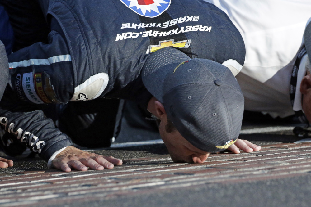 Kasey Kahne (5) kisses the yard of bricks on the start/finish line after winning the NASCAR Brickyard 400 auto race at Indianapolis Motor Speedway in Indianapolis, Sunday, July 23, 2017. (AP Photo/AJ Mast)