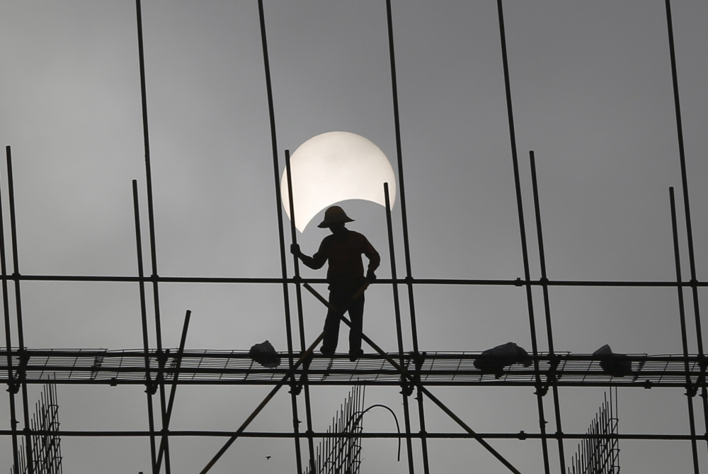A partial solar eclipse at a construction site in Phnom Penh, Cambodia, on March 9, 2016. As eclipse chasers get ready for the Great American Eclipse next month,  many hotels along the prime viewing path are already booked solid.