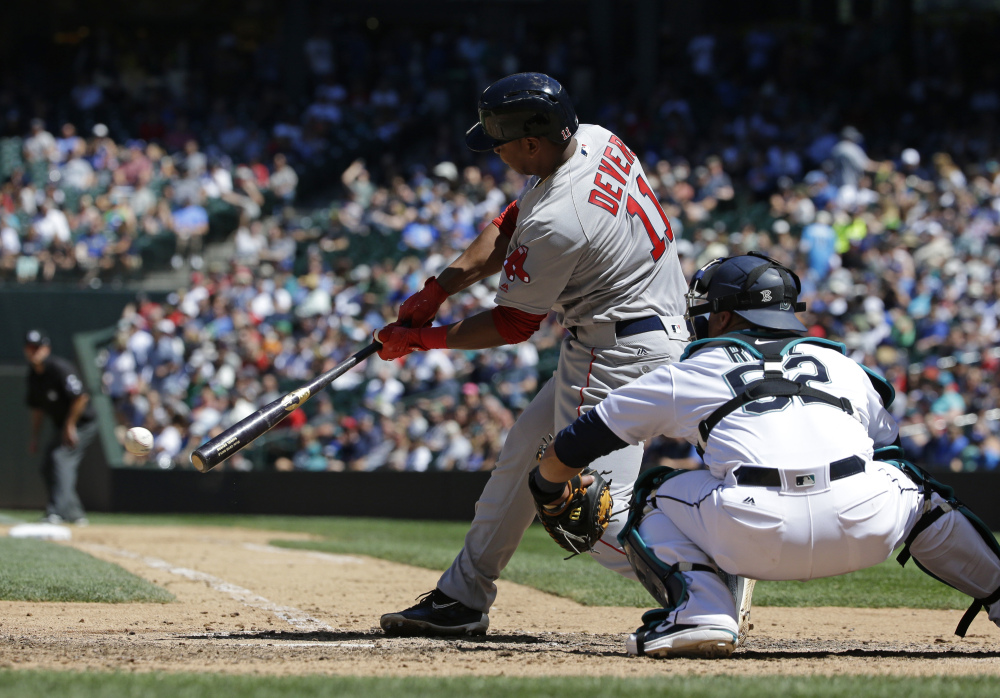 Rafael Devers hits a single in the seventh inning Wednesday at Seattle. Devers homered earlier in the game for his first major league hit.