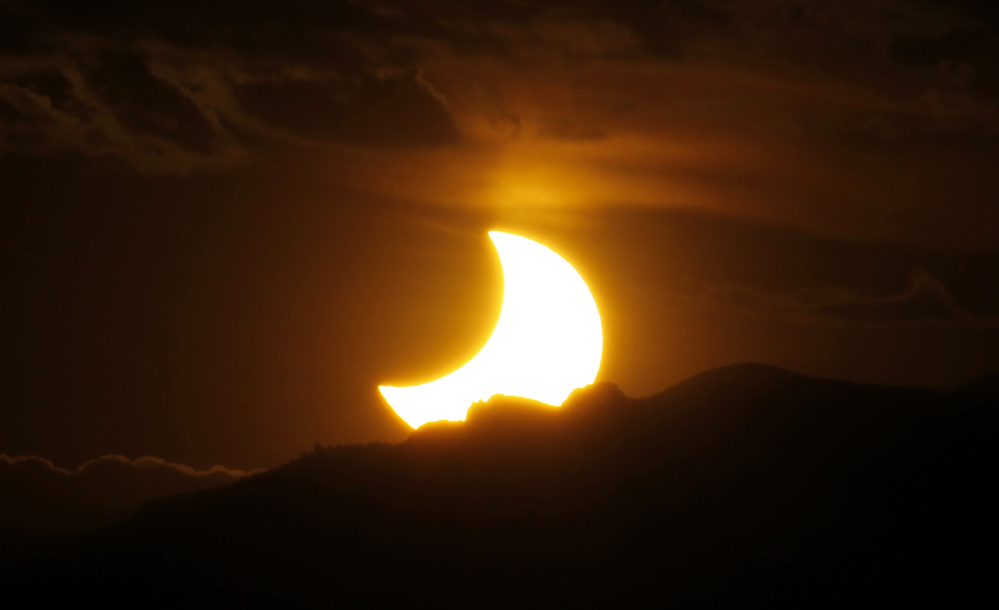 The annular solar eclipse is seen as the sun sets behind the Rockies from downtown Denver on May 20, 2012.