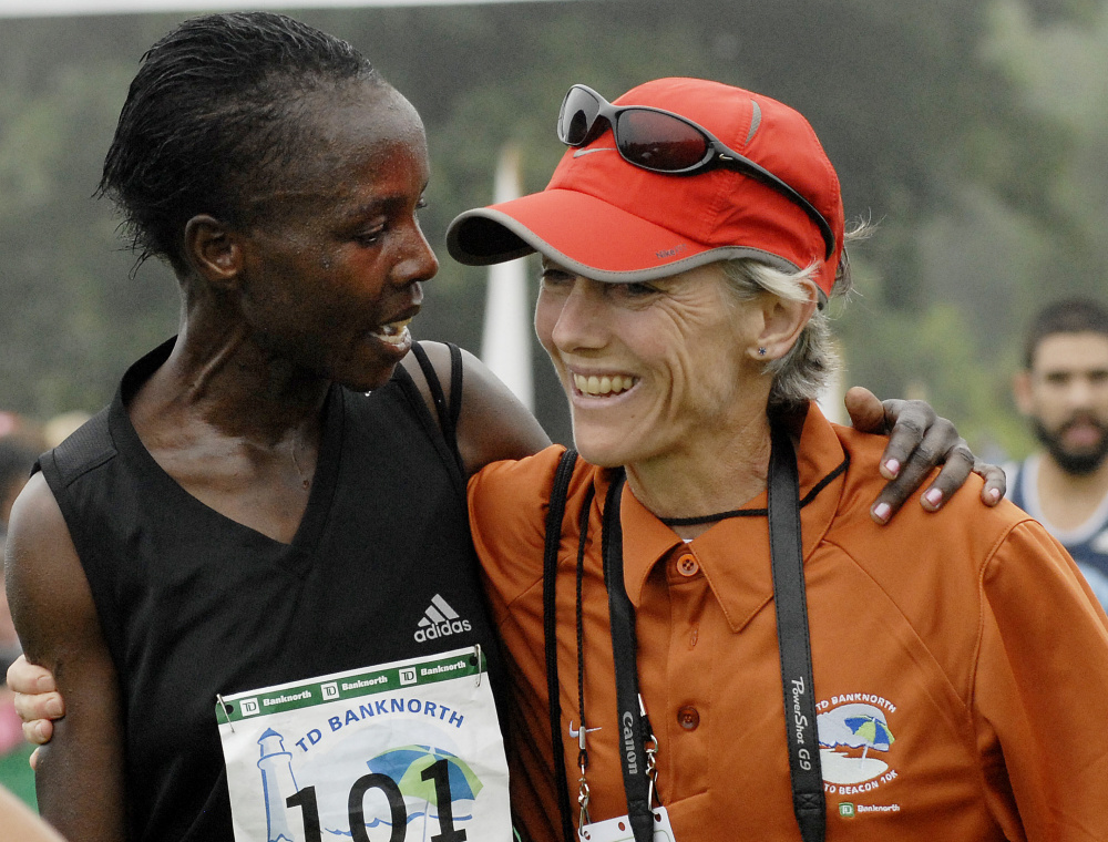 Edith Masai of Kenya is congratulated by Joan Benoit Samuelson after Masai crossed the finish line with the best women's time of the 2008 race by more than seven seconds.