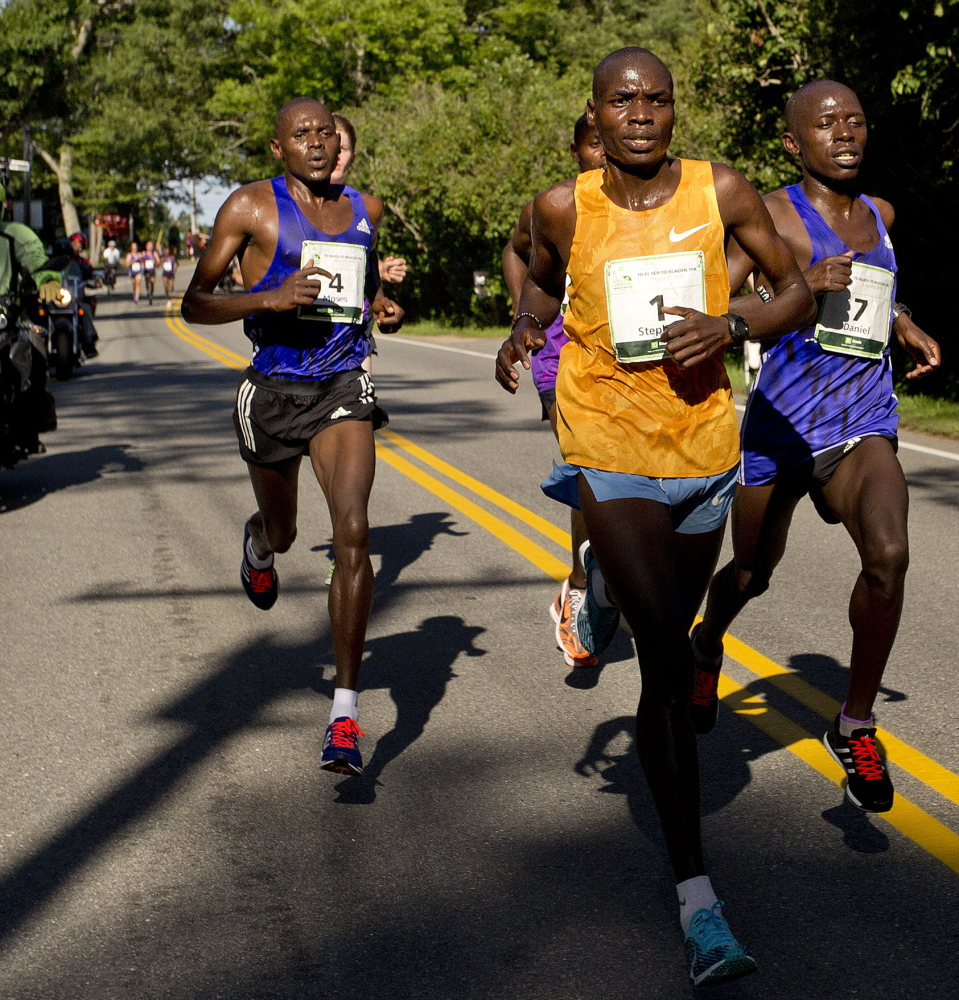 Stephen Koskei Kibet of Kenya, in yellow, leads the pack on his way to a victory after two runner-up finishes.