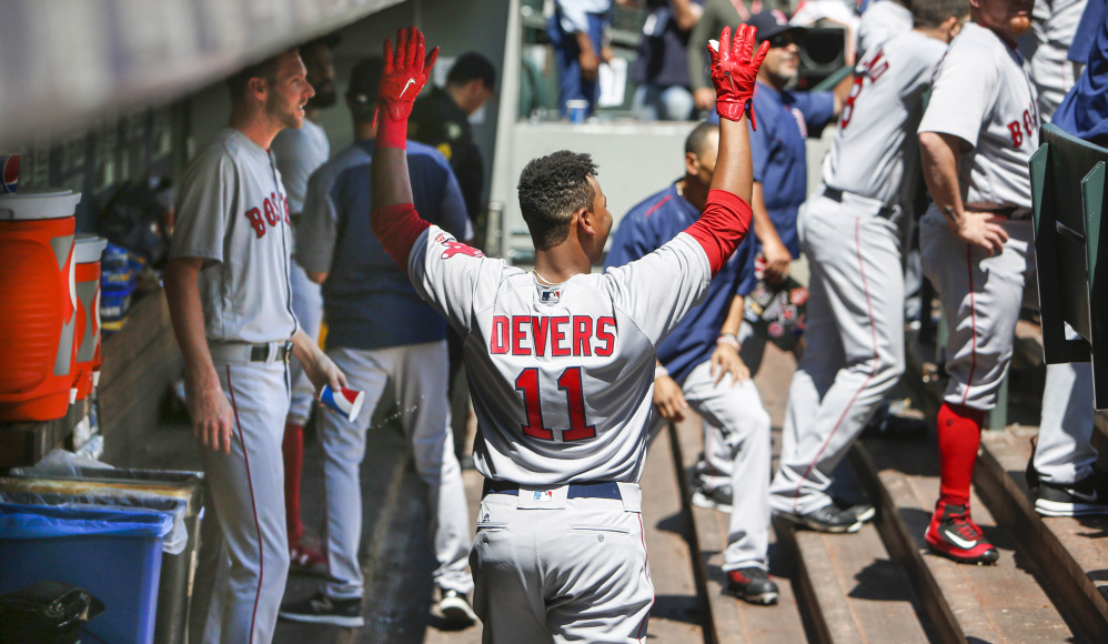 Boston third baseman Rafael Devers is jokingly ignored by teammates in the dugout after hitting his first career home run during the third inning against Seattle. Devers is the youngest player in the major leagues by 73 days.