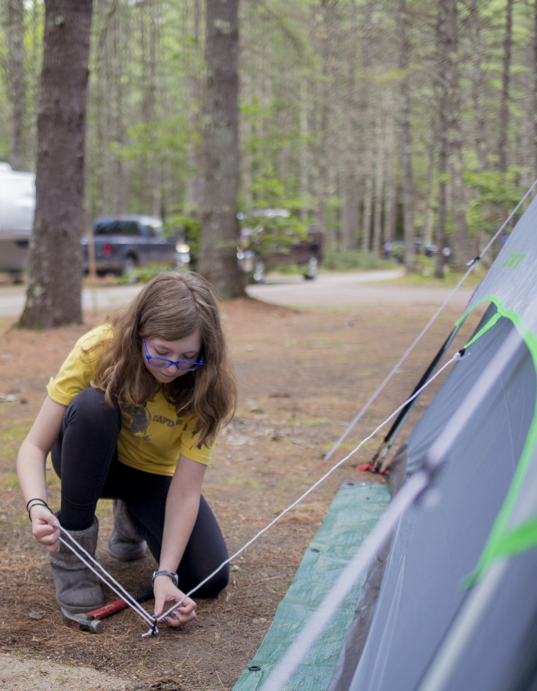 Katelyn Mitchell helps set up the tent with her dad, Steve Mitchell,  at Sebago Lake State Park. The pair came up from their home in Rhode Island for a few days of camping.