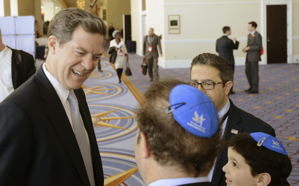 A staunch conservative, Kansas Gov. Sam Brownback, shown with a group from the Young Jewish Conservatives, is expected to garner Senate confirmation for his new post.