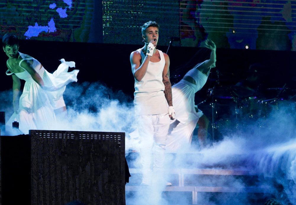 "FILE - In this Sept. 29, 2013, file photo, Justin Bieber performs on a stage during his world tour concert in Beijing. Beijing said it won't be inviting Justin Bieber to perform in China because of his past ""bad behavior,"" although it did concede that the Canadian singer has talent. In response to a question from a purported fan on its web page, the Beijing Municipal Bureau of Culture said it was acting in the interest of imposing standards and order and ""cleaning up"" the domestic performance market. (Chinatopix via AP, File)"