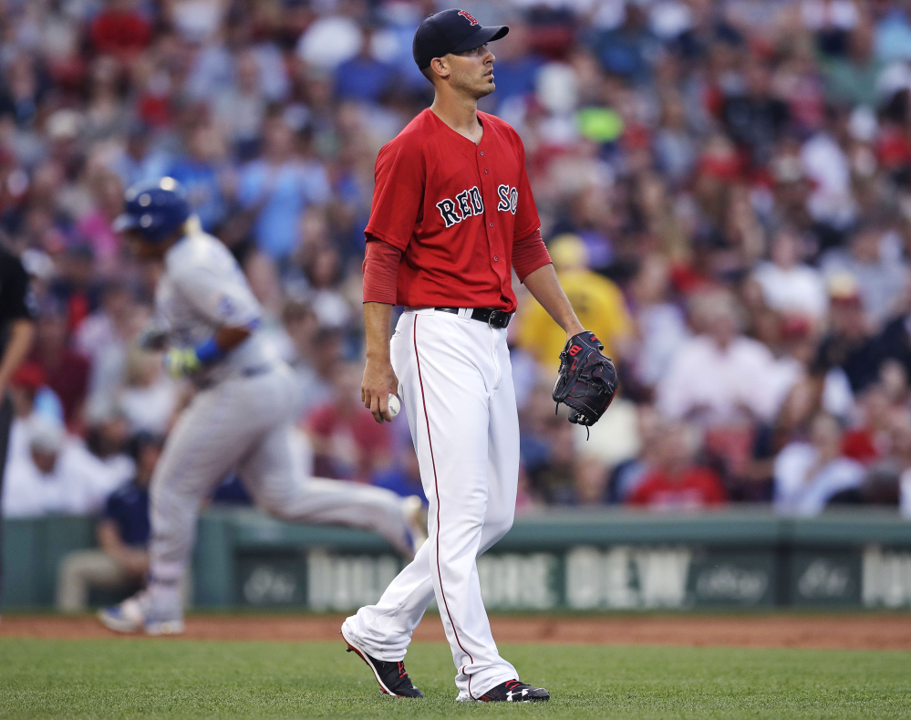 Red Sox starter Rick Porcello walks away from the mound with a fresh baseball as Kansas City's Salvador Perez rounds the bases after a solo home run in the second inning Friday night at Fenway Park.