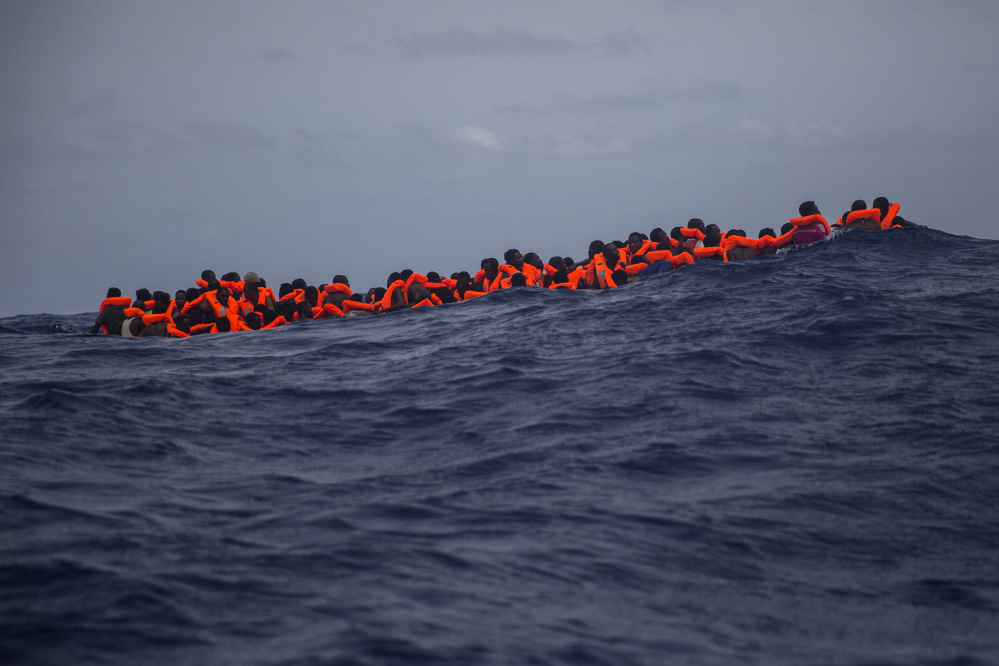 Sub saharan migrants wait to be rescued by aid workers of Spanish NGO Proactiva Open Arms in the Mediterranean Sea, about 15 miles north of Sabratha, Libya on Tuesday, July 25, 2017. More than 120 migrants were rescued Tuesday from the Mediterranean Sea while 13 more —including pregnant women and children— died in a crammed rubber raft, according to a Spanish rescue group. (AP Photo/Santi Palacios)