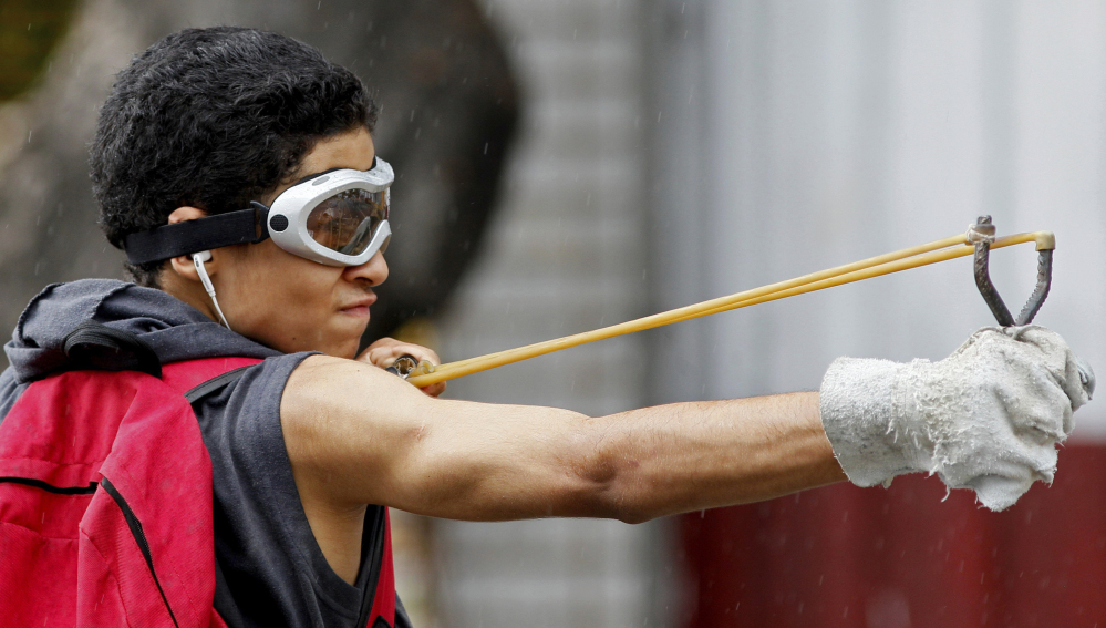 An anti-government protester launches marbles from a slingshot Friday at National Guards in Caracas, Venezuela.