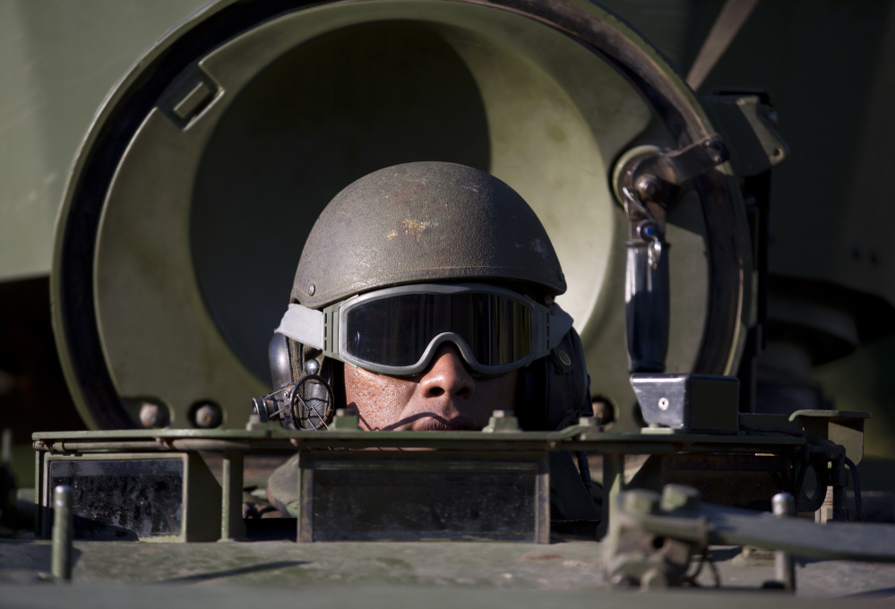 A Navy soldier patrols in an armored vehicle near Santos Dumont Airport, one of the quieter areas in Rio de Janeiro, Brazil, on Friday.