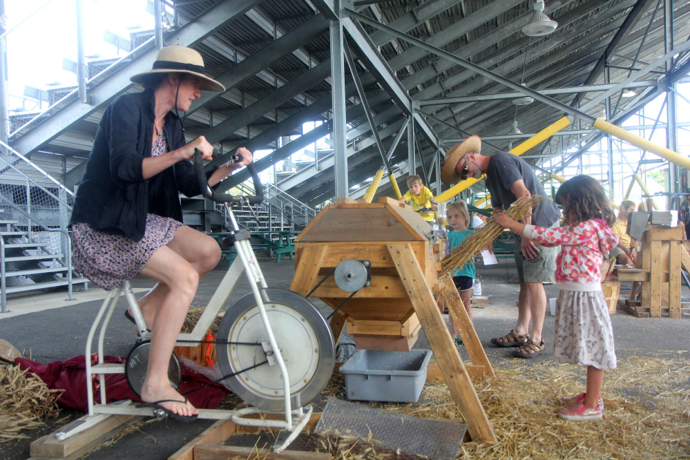 Emily Vogler of Westport, Mass., works a wheat thresher Saturday with her 4-year-old daughter, Lucia Yoder, at the annual Artisan Bread Festival at the Skowhegan fairgrounds.