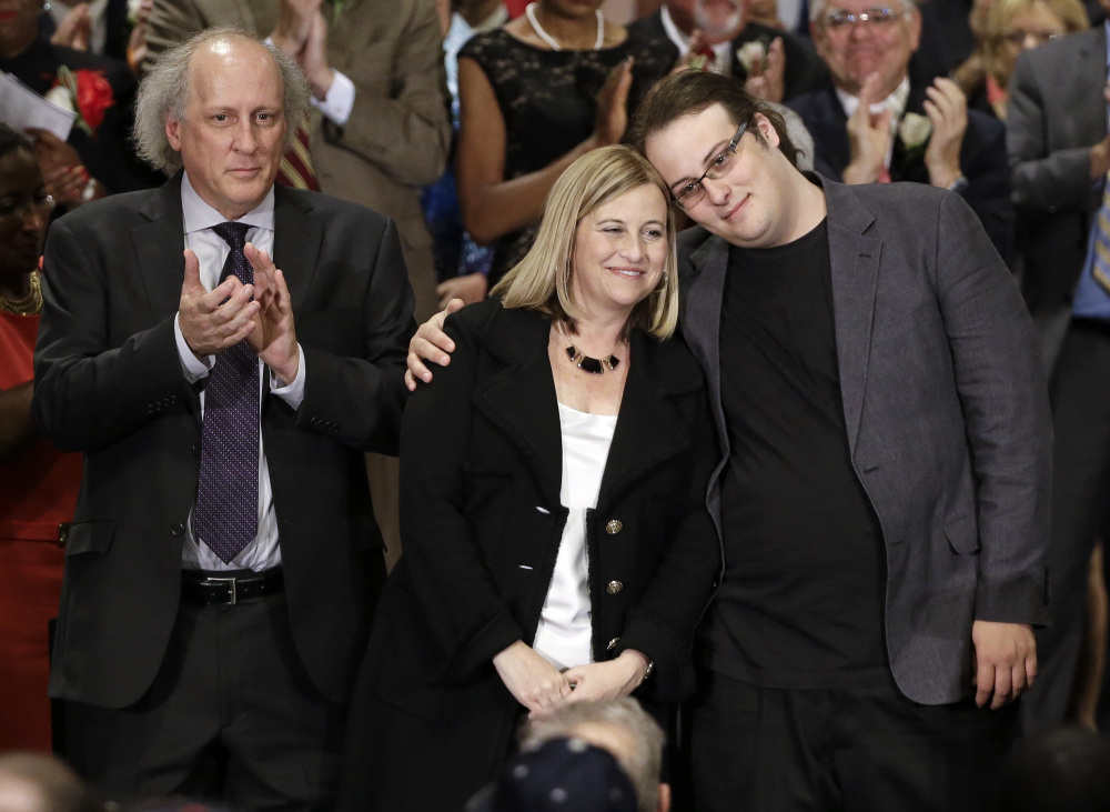Nashville Mayor Megan Barry is hugged by her son, Max, as her husband, Bruce, left, applauds after she was sworn into office in 2015.