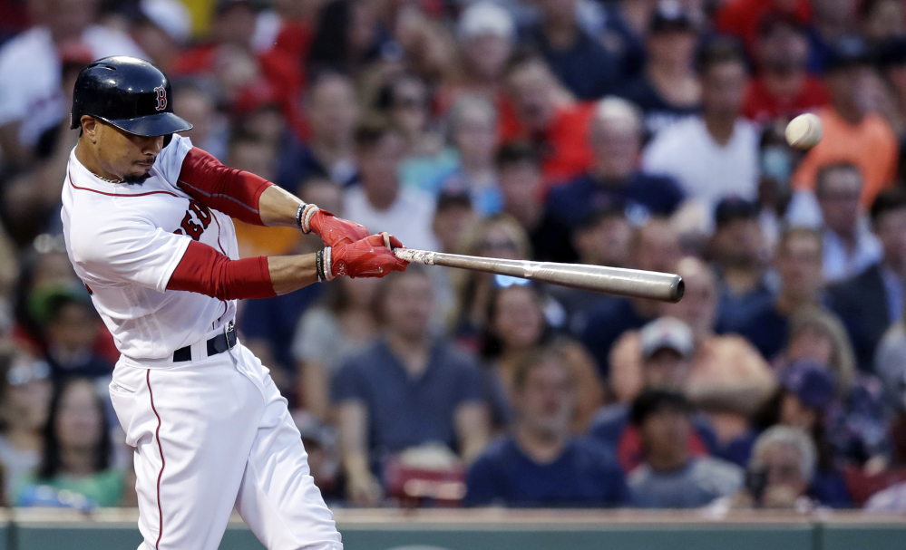 Mookie Betts connects for a two-run single in the second inning of Monday night's game against Cleveland. He finished with two hits and three RBIs in the game.