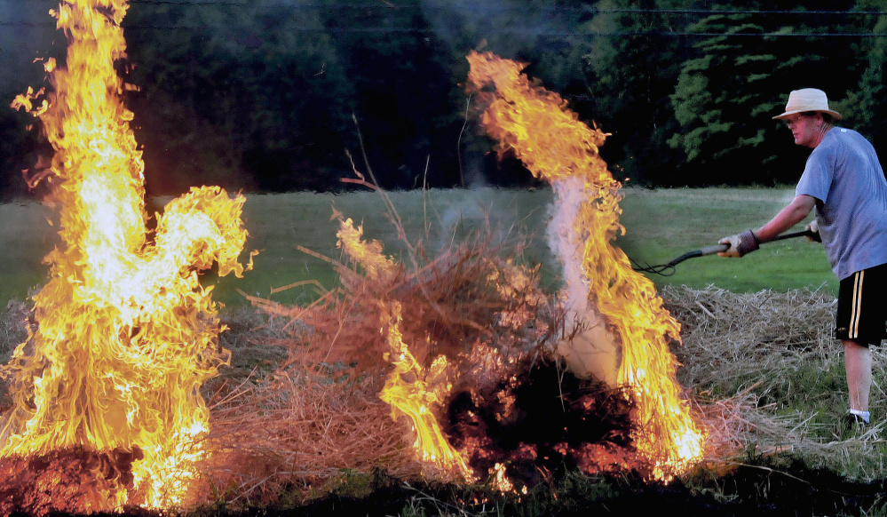 Peter Clifford throws a pitchfork full of burning brush to ignite another pile while he and his father, Roger, burn a field Aug. 25, 2014, in Benton.