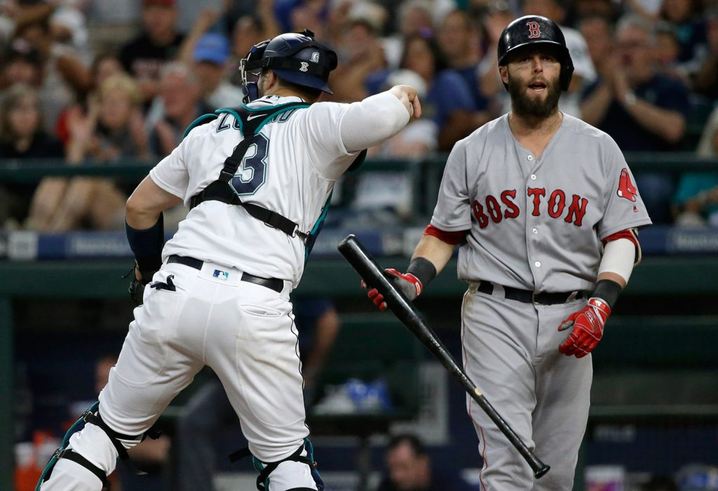 Boston's Dustin Pedroia, right, reacts to striking out swinging as Seattle Mariners catcher Mike Zunino returns the ball during the sixth inning Monday.