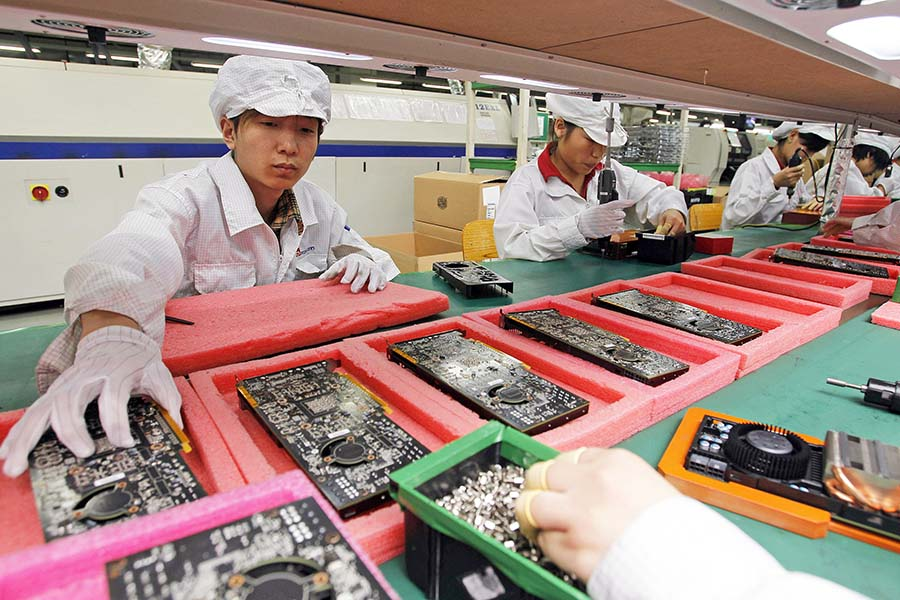 staff members work on the production line at the Foxconn complex in the southern Chinese city of Shenzhen.