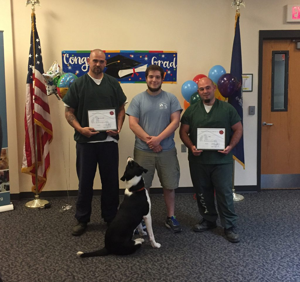 Norman Palmer, Mike Gould and Dustin Campbell, from left, pose with Border Collie mix Jake, one of the first Beyond the Bars graduates, at May's ceremony at Two Bridges in Wiscasset.