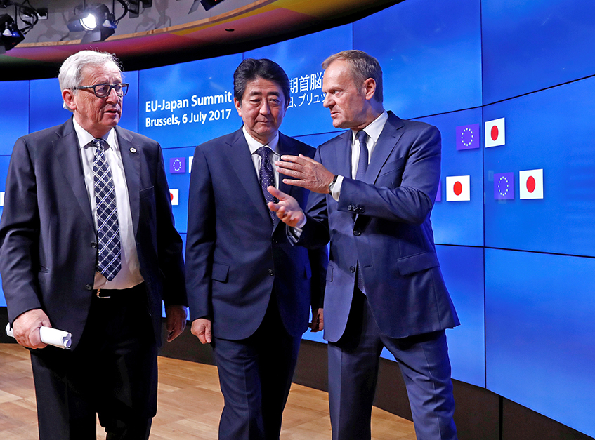 Japan's Prime Minister Shinzo Abe talks with European Commission President Jean-Claude Juncker, left, and European Council President Donald Tusk at the end of a EU-Japan summit in Brussels on Thursday.