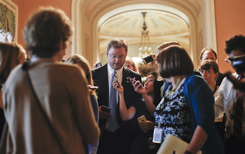 Sen. Dean Heller, R-Nev.,  surrounded by members of the media on Capitol Hill on July 13.