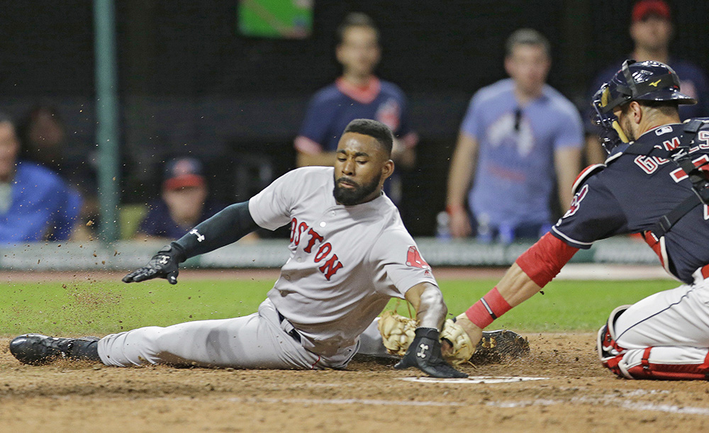 Jackie Bradley Jr. slides safely into home plate as Cleveland Indians catcher Yan Gomes is late on the tag in the seventh inning of Tuesday's game. He sprained his thumb during the slide.
