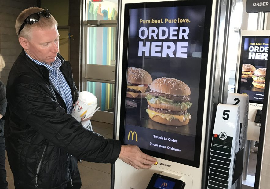 Gorham Road McDonald's owner James Nygren demonstrates functions on a new ordering kiosk last year. The writer says the objection that fast-food restaurants are built on a soulless factory model is a facile argument, and obscures the genius behind the phenomenon.