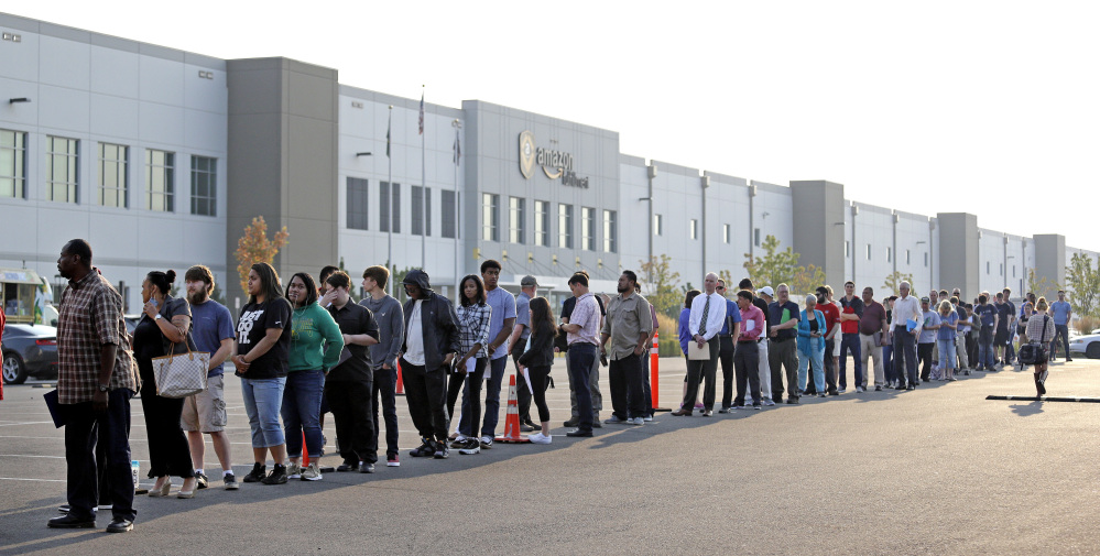 Applicants wait in line to enter a job fair at an Amazon fulfillment center, in Kent, Washington on Wednesday.. Amazon planned to make thousands of job offers on the spot.