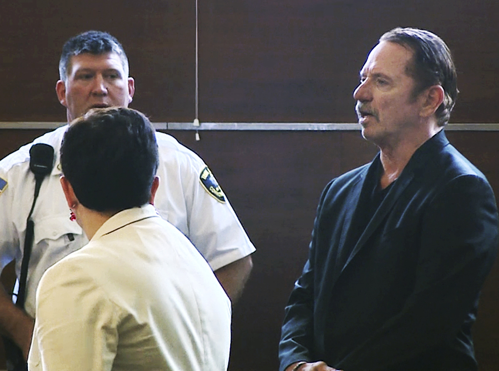 Actor Tom Wopat, right, stands during arraignment Thursday in Waltham, Mass. He was arrested as he was leaving a play rehearsal Wednesday  and is charged with indecent assault. WCVB-TV via AP, Pool